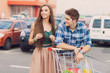 portrait of young couple with shopping cart outdoors