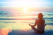 Silhouette of woman at yoga pose on the beach during at sunset.