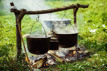 A Group Of Cauldrons And Kettle Are Hanged Upon Fire