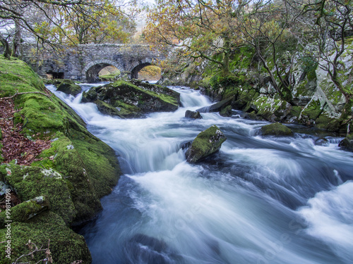 фотография  Ogwen river above Bethesda flowing around mossy rocks with a stone bridge in the background