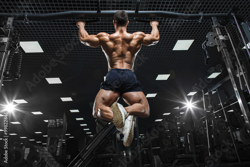 Fotografie, Obraz  Athlete muscular fitness bodybuilder male model pulling up on horizontal bar