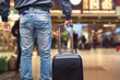uomo con valigia trolley alla stazione per vedere su tabellone gli orari treni per partire