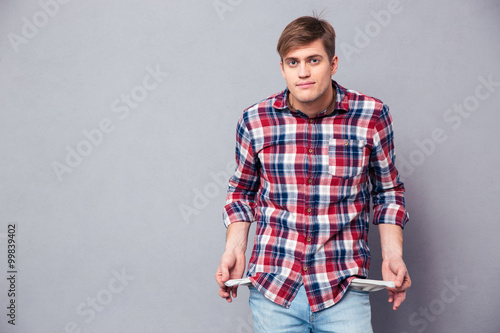 Fotografía  Poor handsome young man in checkered shirt showing empty pockets