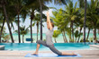 happy woman making yoga in low lunge over beach