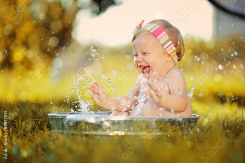 fototapeta na drzwi i meble Маленький ребенок играет в тазике с водой