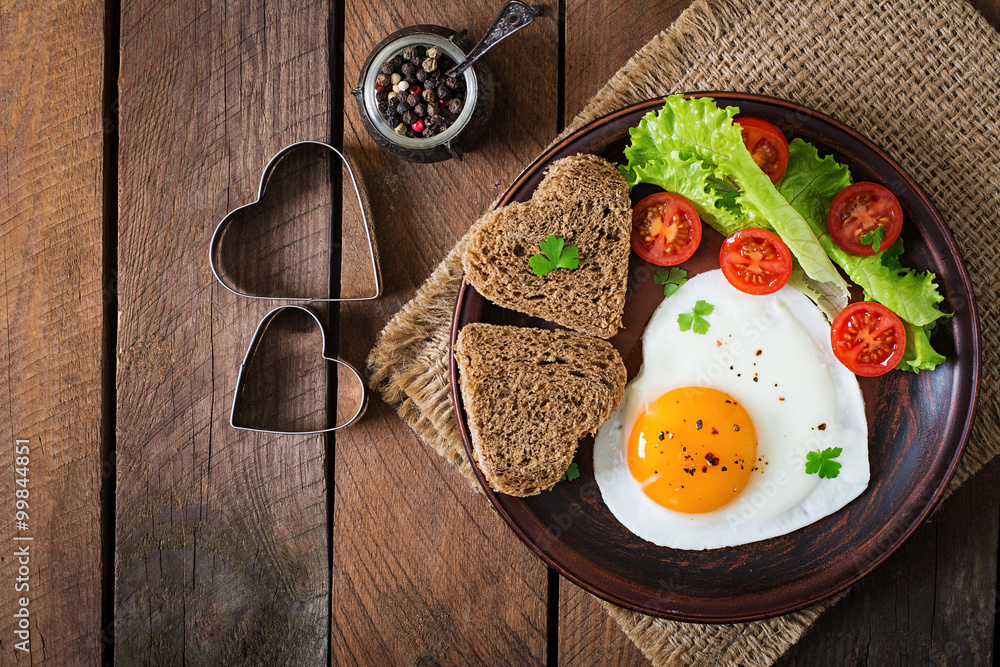 Fototapety, obrazy: Breakfast on Valentine's Day - fried eggs and bread in the shape of a heart and fresh vegetables. Top view