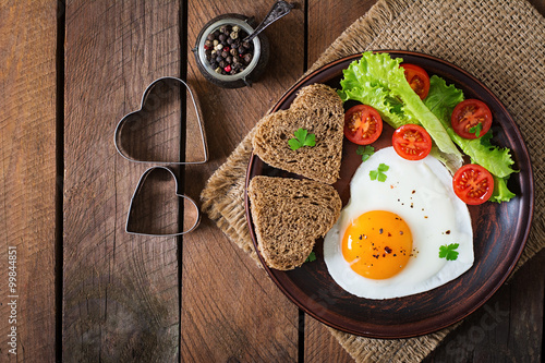 Obraz Breakfast on Valentine's Day - fried eggs and bread in the shape of a heart and fresh vegetables. Top view - fototapety do salonu