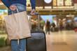 uomo con valigia trolley e borsa shopping che aspetta treno in stazione