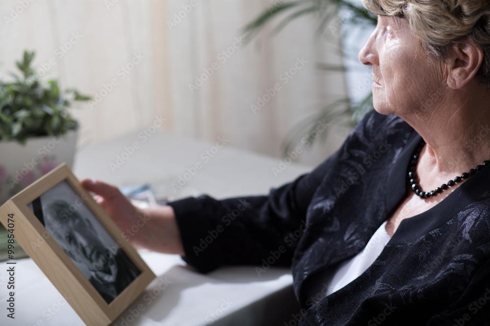 Fototapeta Senior widow reminiscing her husband