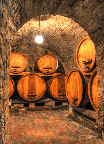 Fotografie, Obraz  View into an old wine cellar with large barrels through an arch