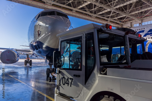 Fotografia  TUG Pushback tractor carries a passenger jet out of hangar