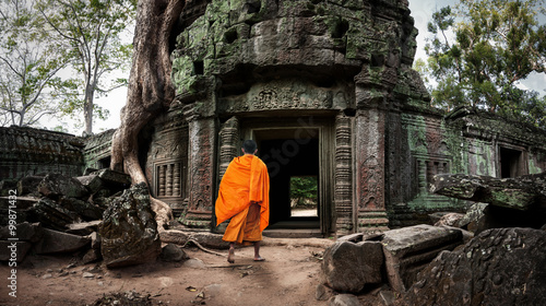 Photo Buddhist monk enters Ta Prom Khmer ancient temple of Angkor Wat site in Cambodia