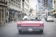 A newlywed married couple is driving a convertible retro car in