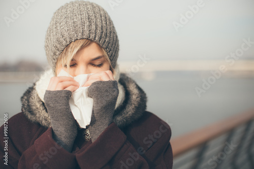Fotografie, Obraz  Young woman with a cold holding a tissue