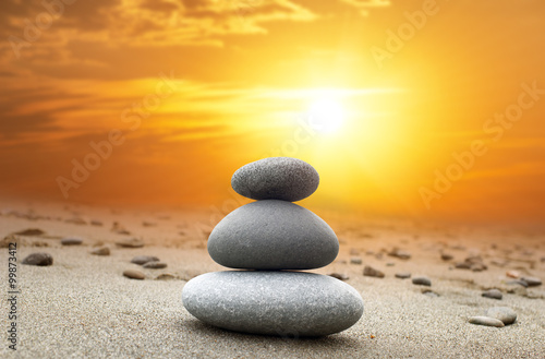 Oriental background of stones pyramid at sunset with bright yellow sun on evening sky