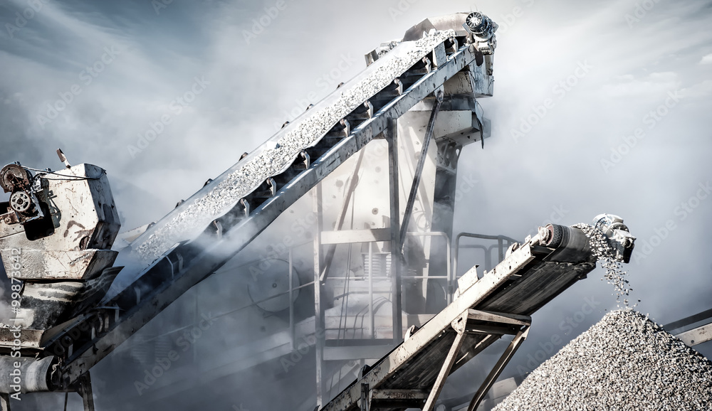 Fototapeta Cement production factory on mining quarry. Conveyor belt of heavy machinery loads stones and gravel