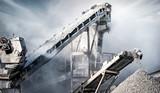 Fototapeta Młodzieżowe - Cement production factory on mining quarry. Conveyor belt of heavy machinery loads stones and gravel