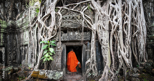 Poster Bedehuis Monk in Angkor Wat Cambodia. Ta Prohm Khmer ancient Buddhist temple in jungle forest