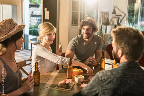 Fotografie, Obraz  Friends having a drink and playing cards on a sunny evening. The