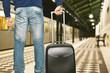 uomo in metropolitana alla stazione che prende il treno con valigia a trolley per andare al lavoro