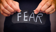 Woman Ripping Fear Word Written On Black Paper