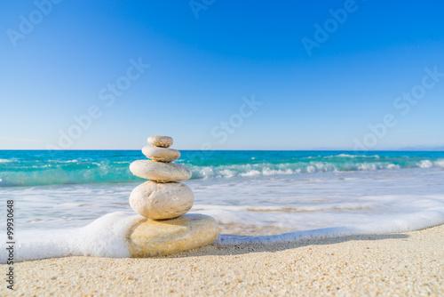 Photo sur Plexiglas Zen pierres a sable Stones pyramid on sand symbolizing zen, harmony, balance. Ocean