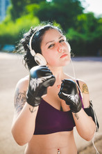 Half Length Of A Sportive Young Mixed Race Curly Black Hair Woman Boxer Training In The Suburbs, Posing Prepared To Fight Listening Music With Headphones - Sportive, Strength, Healthy Concept
