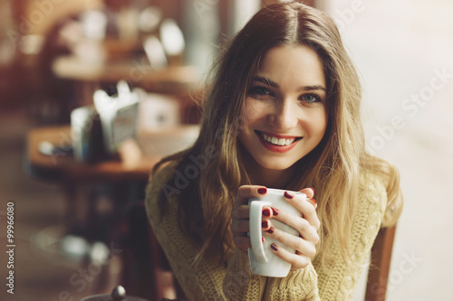 Canvas Print Charming girl drinking cappuccino and eating cheesecake
