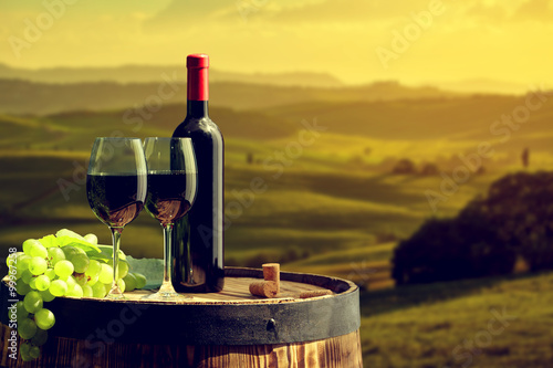 Red wine bottle and wine glass on old barrel.