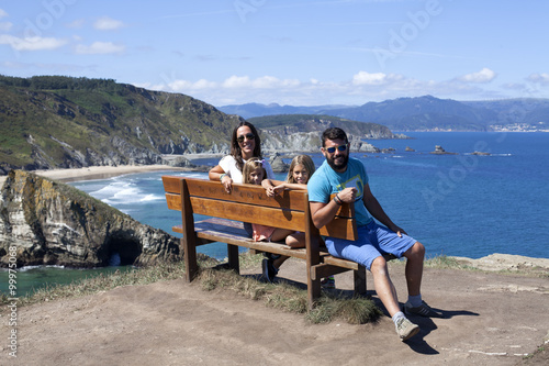 Familia sentada en banco junto a acantilado marino