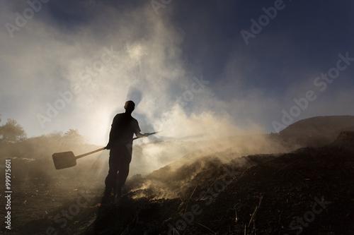 Carta da parati Silhouette of coal man working at sunset in smoke