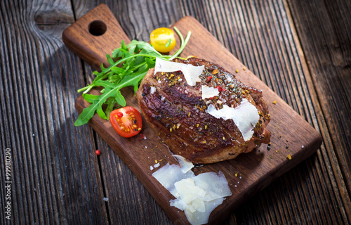 Beef steak on a wooden table. Poster