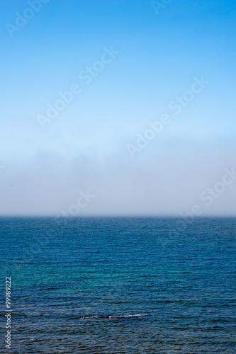 Staande foto Zee / Oceaan Fog low over wavy water under blue sky