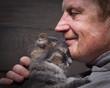 Leinwandbild Motiv Мужчина и кот - два профиля. Морда кота и лицо мужчины. Мужчина в морщинах. Кот и хозяин улыбаются. Кошка ласково прижимается. Любовь кошки и человека. Отношения, ласка. Фон - деревянная доска