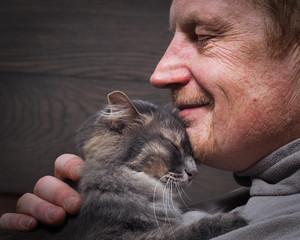 Мужчина и кот - два профиля. Морда кота и лицо мужчины. Мужчина в морщинах. Кот и хозяин улыбаются. Кошка ласково прижимается. Любовь кошки и человека. Отношения, ласка. Фон - деревянная доска