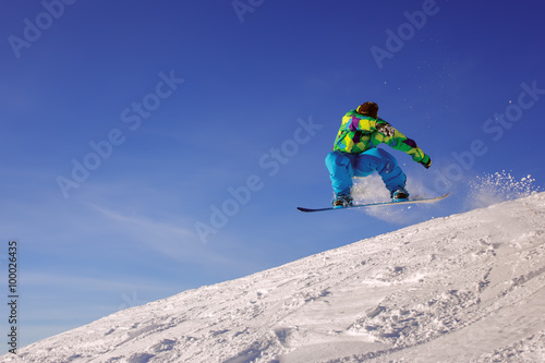 Poster Glisse hiver Snowboarder jumping through air with deep blue sky in background