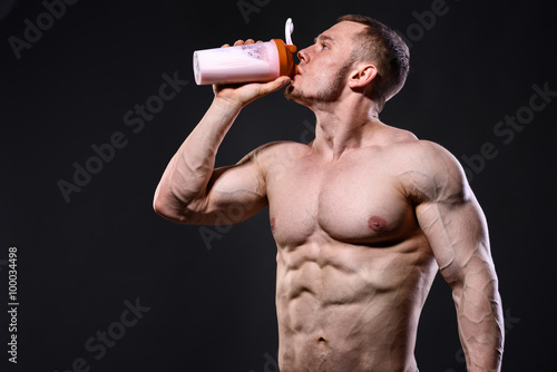 plakat Athlete man drinking protein over dark background