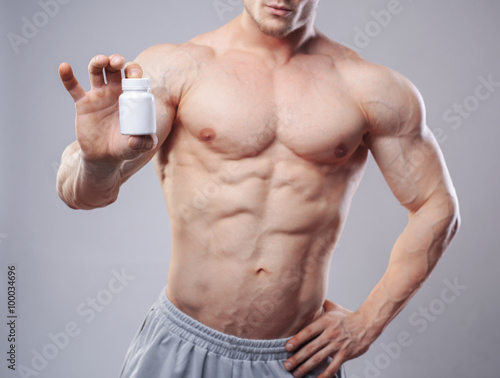 Fotografia  Bodybuilder with a white jar of pills on neitral background