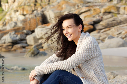 Fotografía  Amiling woman sitting outdoors in sweater