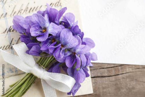 Obraz na płótnie Bouquet of violet flowers (viola odorata) and vintage letters