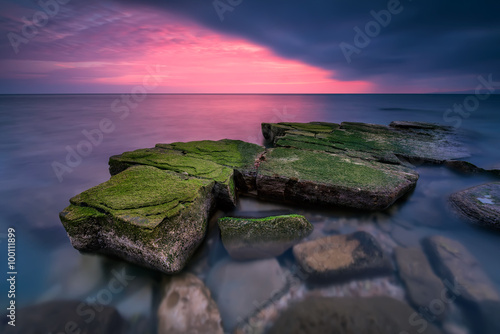 Sea rocks at sunset. Magnificent sunset view in the blue hour at the Black sea coast, Bulgaria.