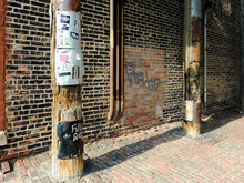 Telephone Poles Against Brick ...