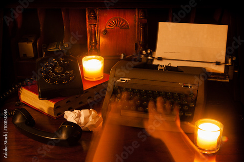 Photo  Ghost hands type on a vintage typewriter with candles, a book, and an old rotary