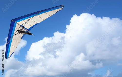 Cadres-photo bureau Aerien Hang Glider – Hang Glider flying through the sky white puffy clouds