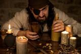 Garstiger Pirat mit Rum sitzt an einem alten Tisch mit vielen Ke