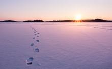 Footprints Leading Towards Sunset On Frozen Lake