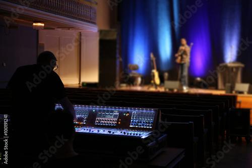 Fotografie, Obraz  Mischpult mit Musiker im Hintergrund
