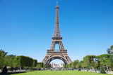 Fototapeta Eiffel Tower - Eiffel tower, sunny summer day with blue sky and green Field of Mars