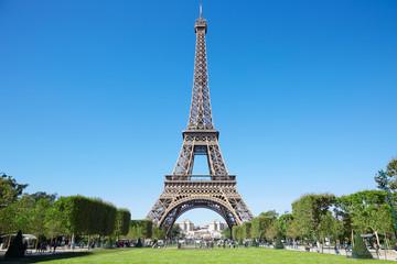 Wieża Eiffla, słoneczny letni dzień z niebieskim niebem i zielonym polem Marsa