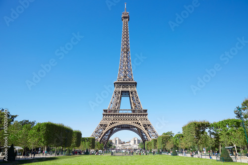 Fotobehang Eiffeltoren Eiffel tower, sunny summer day with blue sky and green Field of Mars